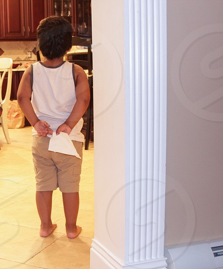 boy in white tank top brown shorts standing on white floor tile beside white wall in room photo