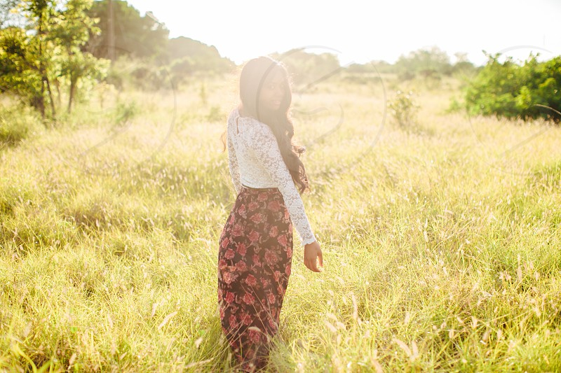 woman in white lace blouse and pink skirt walking through grass photo