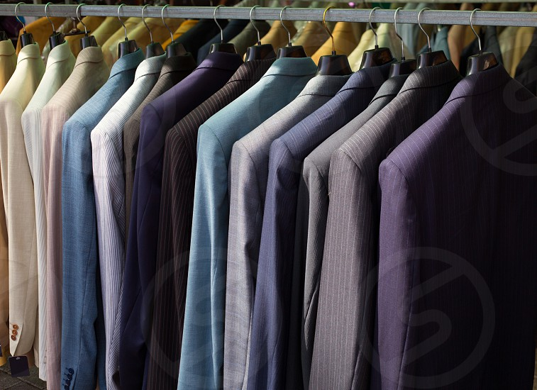 colorful male suits in row in a hanger as a pattern photo