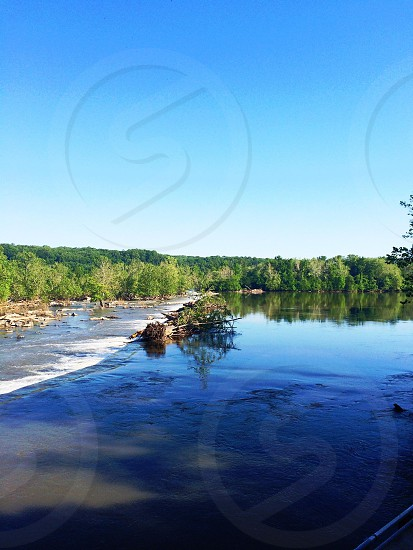 body of water and green trees under blue sky photo