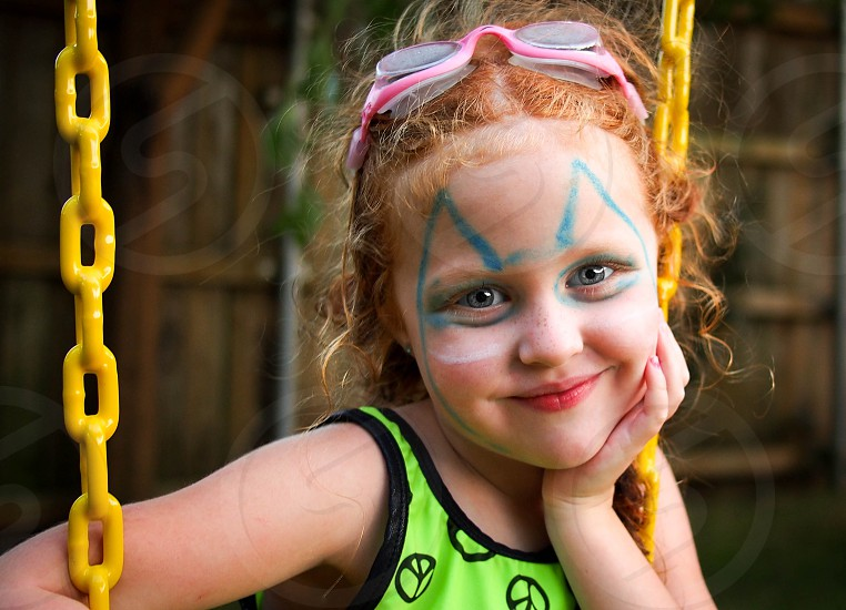 Swinging smiling girl with face paint. photo