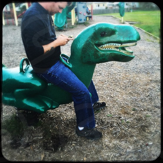 man siting on green T-Rex playground toy photo