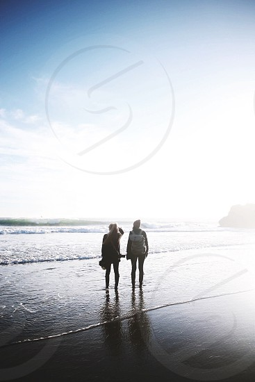 two persons standing on the shore under blue clear sky photo