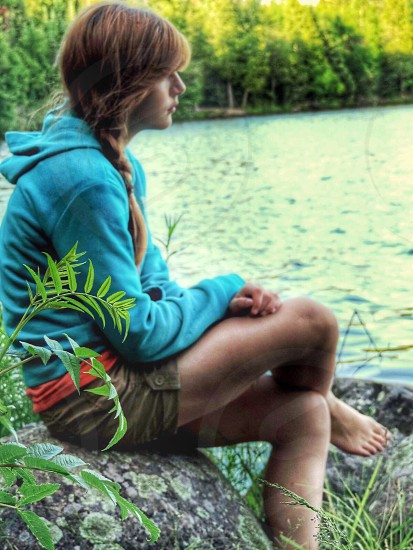 woman wearing teal hoodie and brown shorts while sitting on a rock near lake photography photo