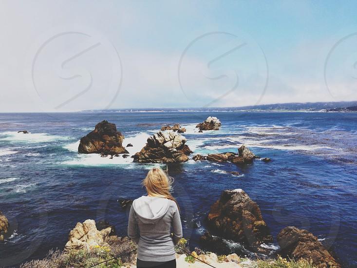 woman in gray hoodie overlooking ocean photo