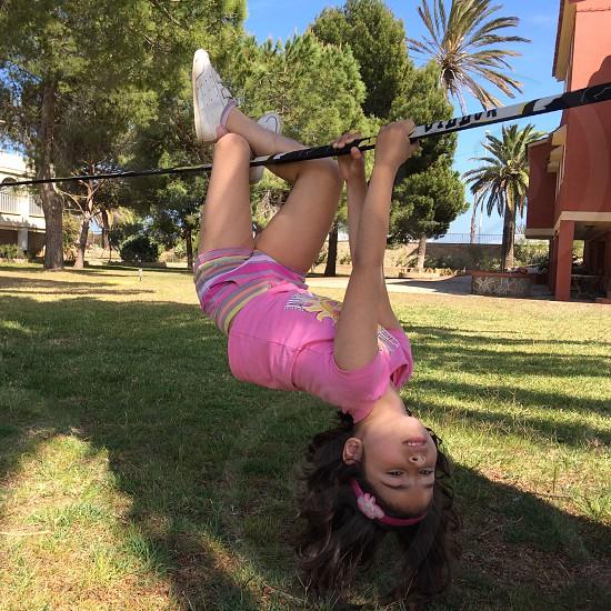 girl hanging of a slack line. Outdoors summer kid.  photo