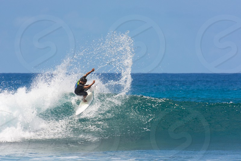 surfer surfing surf wave board green aqua blue water cloudless clear sky tropical splash whitewater spray off the lip tail slide sunny bright photo