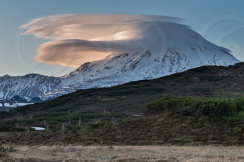 Beautiful clouds over the volcano at sunset. Active Ichinsky Volcano Kamchatka Peninsula Far East Russia Eurasia. photo