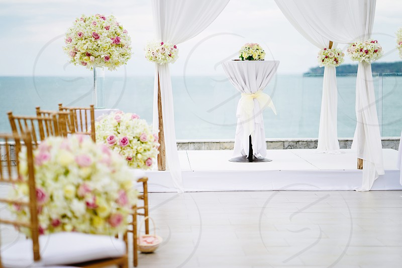 The wedding venue on the hill with panoramic ocean view The arch in white decorated with roses flowers floral. Koh Samui Thailand. photo