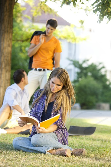 Friends sitting on grass and studying photo
