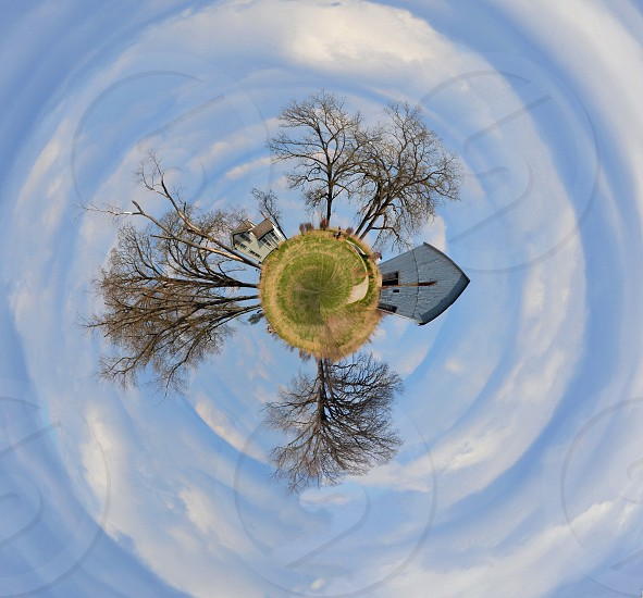 My Own Little World - A planet image of a farm house barn and trees under a swirl of clouds in a blue sky. photo