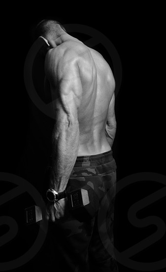 Muscular man training biceps and showing triceps photo