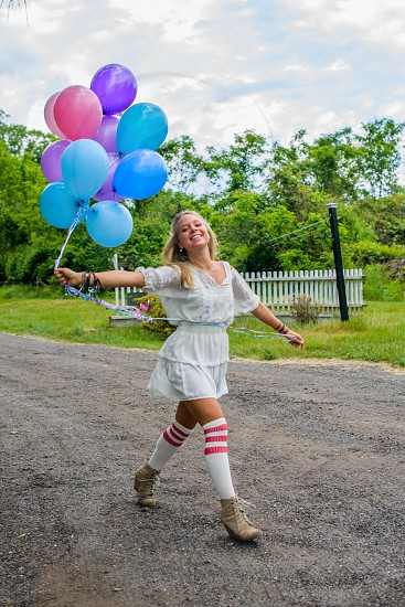 woman wit white dress holding balloons photo