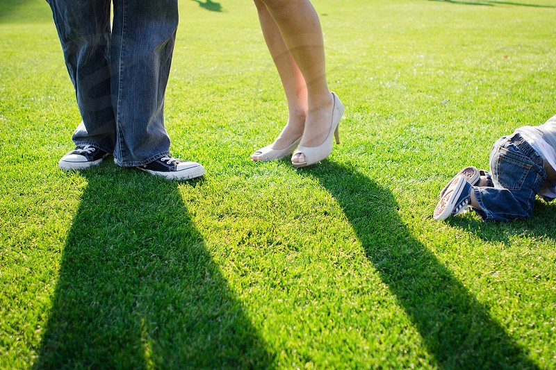couple standing side by side on green trimmed grass lawn beside crawling toddler photo