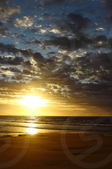 reflection of the sun in clouds at sunrise on the beach photo
