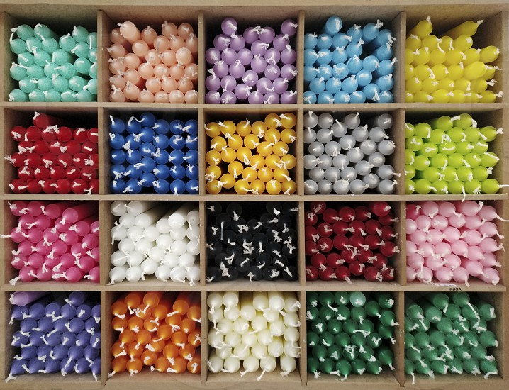 colored candles inside wooden display boxes photo