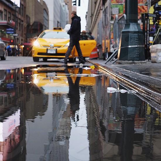 man walking beside yellow taxi photo