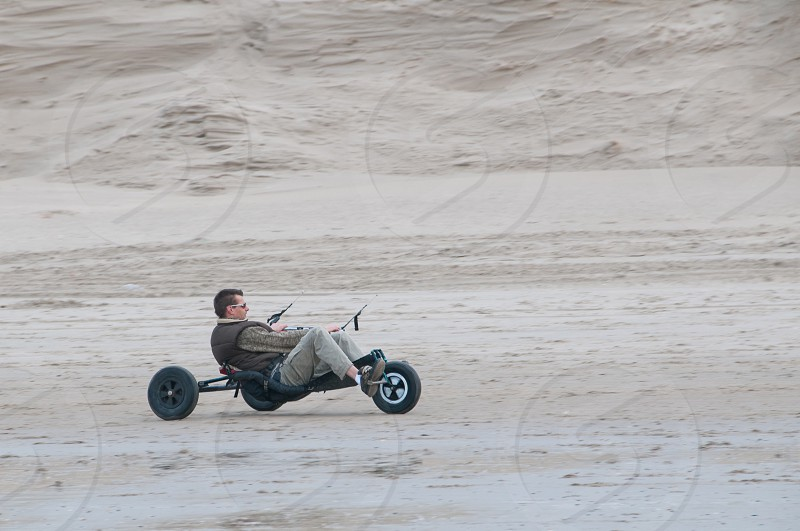 man in gray and black crew neck shirt riding black tricycle on white sandy beach during daytime photo