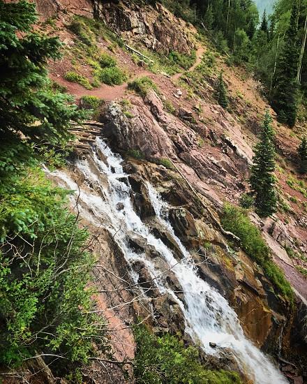 Dirt mountain trail thru waterfall photo