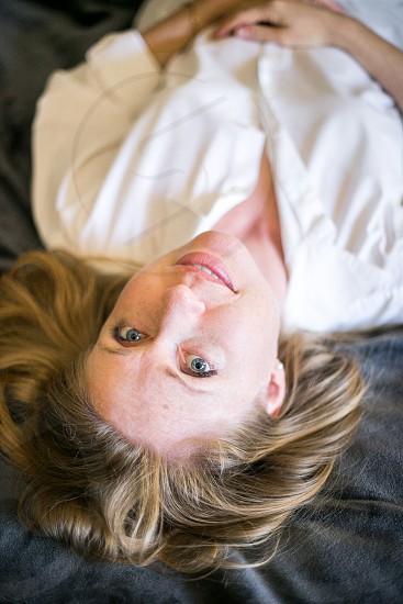 A young woman laying on her back on the bed upside down with a slight smile while looking at the camera. Blouse hair pearl earrings Caucasian girl lady relaxed comfortable natural honest home blue bed blanket white. photo