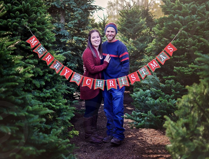 Couple in a Christmas tree lot - Merry Christmas sign photo