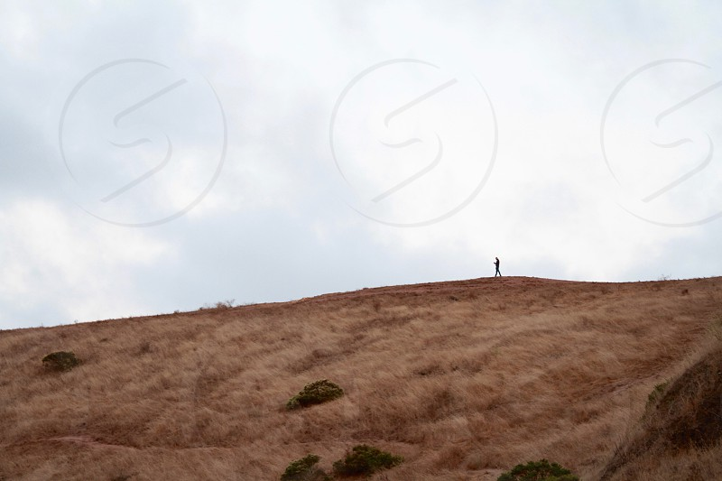 silhouette of person walking on hill under white sky photo