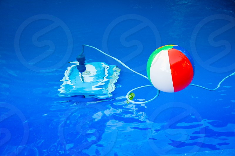 Colorful beach ball floating in pool and next to him underwater a cleaning robot. photo