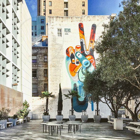 Plaza tables and chairs trees peace mural photo