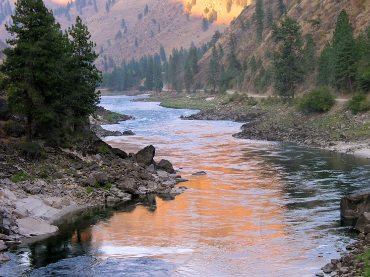 Sunset and reflection of sun in river of deep canyon photo