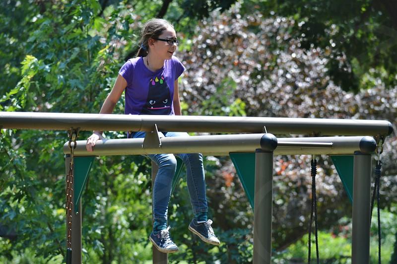 woman sitting on metal pole photo
