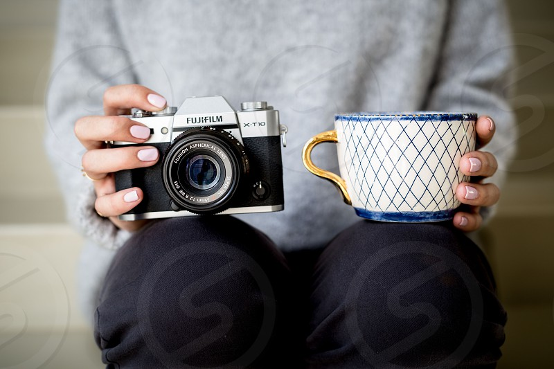 A young female photographer/entrepreneur sits with a camera balanced on one knee and a coffee cup on the other. photo