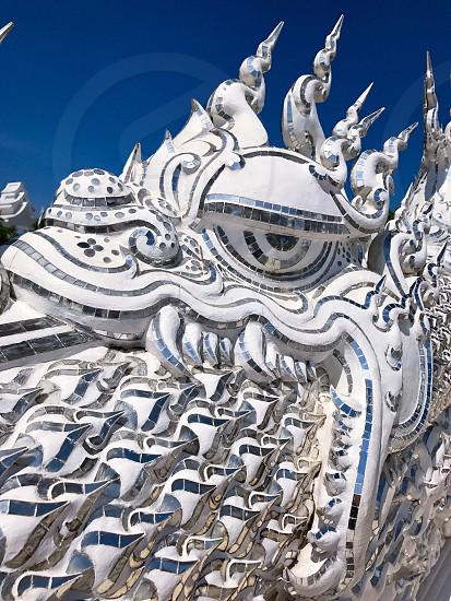 Outdoor day vertical portrait colour Wat Rong Khun The White Temple Chiang Rai Thailand Thai Kingdom of Thailand travel tourism tourist wanderlust summer summertime temple Buddhist Buddhism spiritual pure holy dragon monster carved ornate elaborate art modern sculpture sculpted east eastern hands silver mirror mosaic magical mythical blue sky dragon eye shine photo