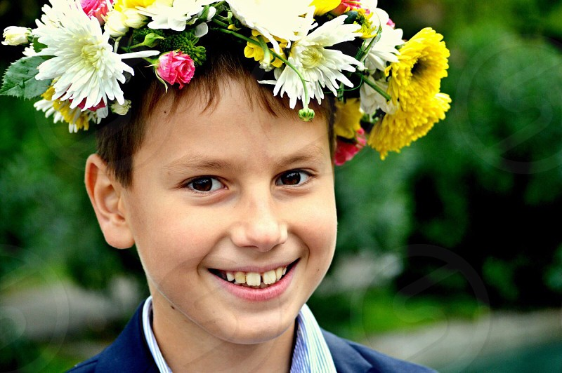 boy wearing blue polo shirt with white yellow and red flower hair dress photo
