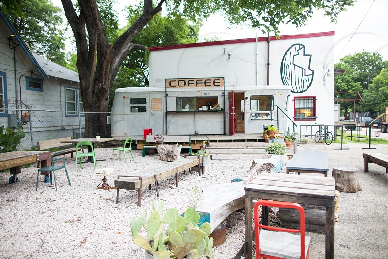red metal frame chair beside gray wooden table near brown wooden bench in front of coffee sign white concrete building during daytime photo