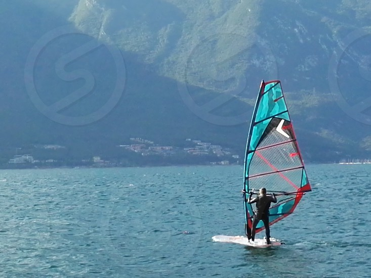 person in black wet suit windsurfing near green mountain during daytime photo