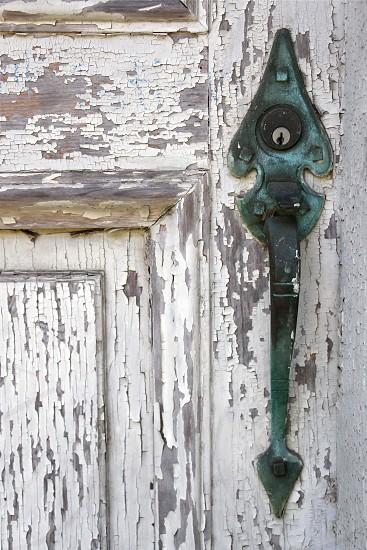 green door handle on white wooden  door photo