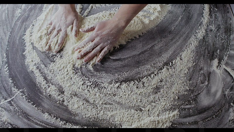 Chef woman's hands gather fresh natural flour on kitchen background. Slow motion Full HD video 240fps 1080p. Step by step homemade dough preparation. Top view. photo
