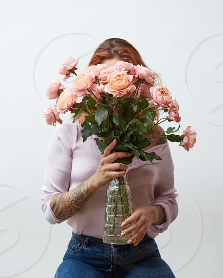 Red-haired girl with a tattoo and a beautiful pink bouquet of roses in a vase on a gray background with copy space. Mothers Day. photo