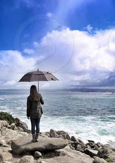 Woman Standing Looking  at Ocean after the Rain photo