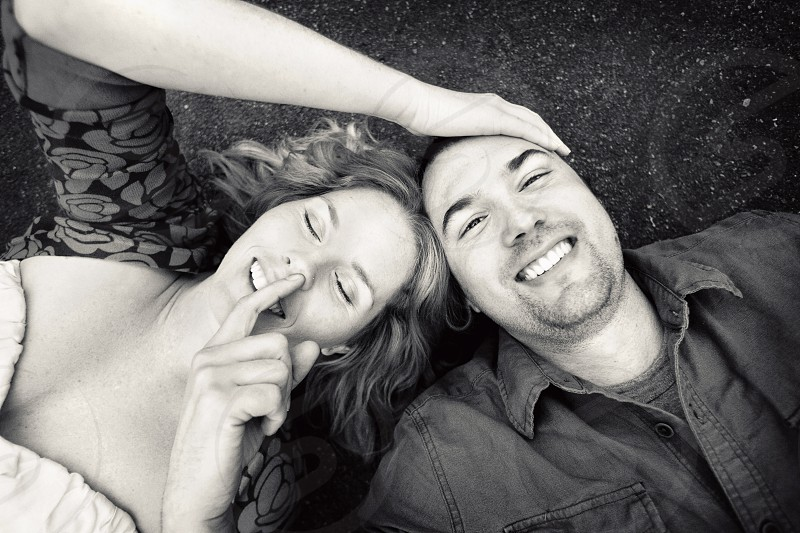 Young couple lies on a road smiling as she touches his face and he picks her nose. photo
