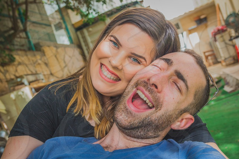Young couple enjoying together in the backyard. They are smiling laughing and making funny faces together. photo