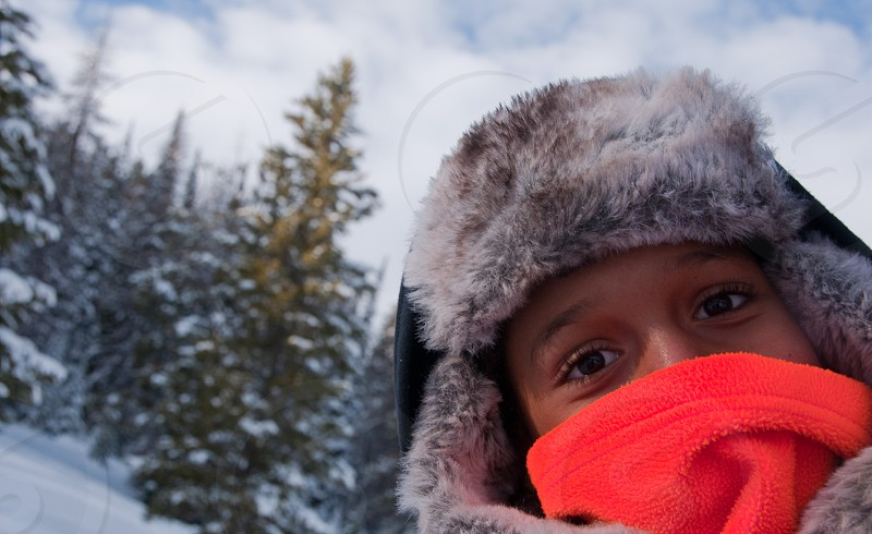 smiling brown-eyed brunet person wearing fur-trim ear-flap hat and orange fleece muffler by snow-covered coniferous forest beneath white cloudy sky photo