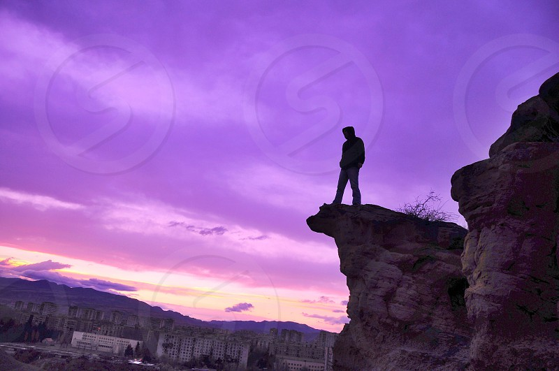man standing on rock cliff photo