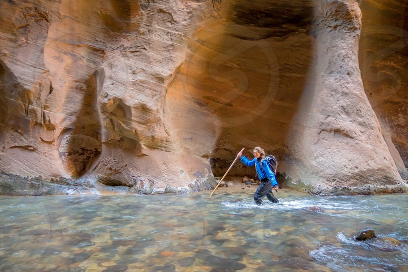 woman in blue jacket hiking through water cave with stick photo