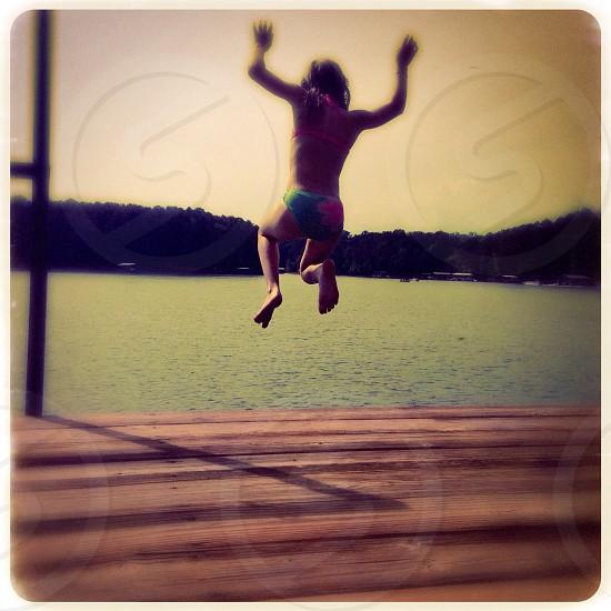 Girl jumping into lake photo