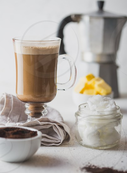 BULLETPROOF COFFEE. Ketogenic keto diet coffe blended with coconut oil and butter. Cup of bulletproof coffee and ingredients on white background. photo