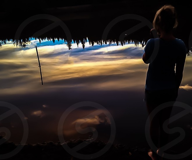 woman in blue shirt looking at sky reflection in lake photo