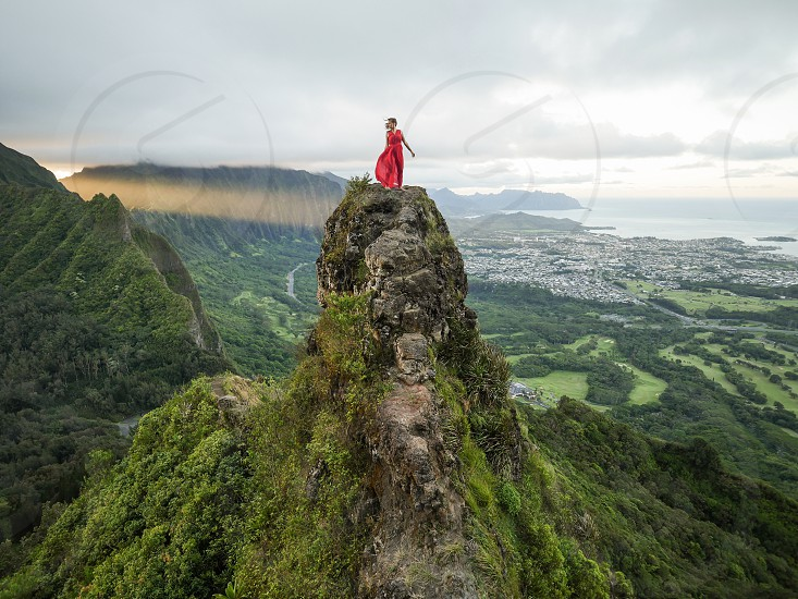 Woman with red dress standing on a peak of a mountain in Hawaii nature environment lifestyle outdoors hike  photo