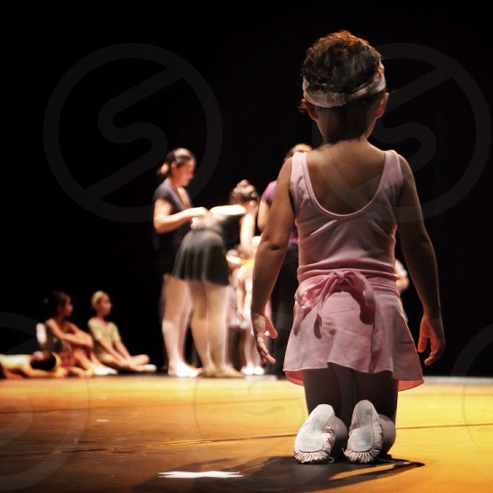 girl in pink ballerina outfit kneeling on a stage photo