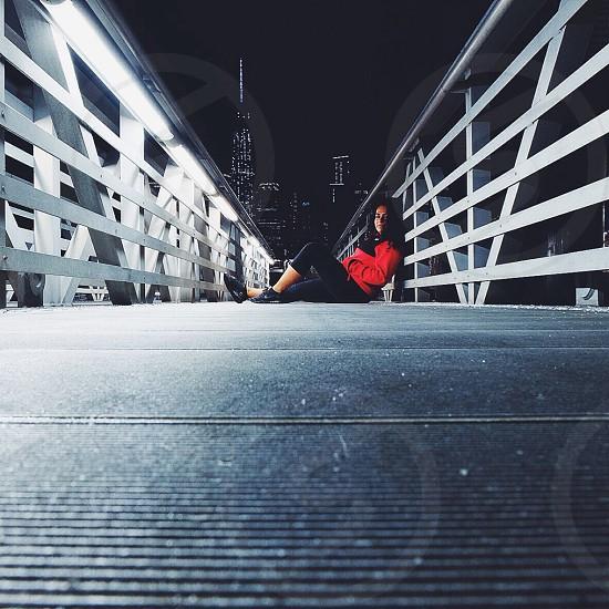 woman in black capri pants sitting on footbridge photo